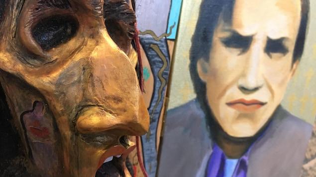Une sculpture du visage d'un homme est en avant-plan avec une peinture d'un homme en arrière-plan.