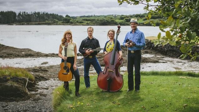 Les quatre membres du groupe The Foghorn Stringband posent près d'un lac avec leurs instruments.