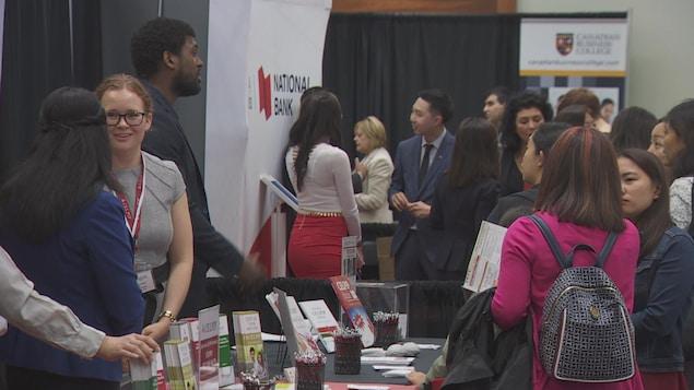 Des immigrants récemment arrivés en Ontario échangent lors d'une foire sur l'emploi au centre-ville de Toronto.