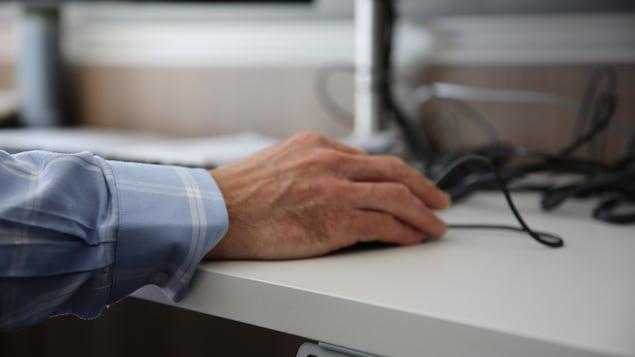 Une main sur une souris d'ordinateur.