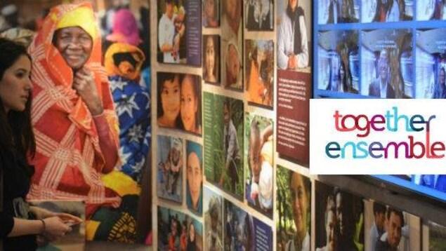 Une dame est debout devant des images et des photos de l'exposition Ensemble.