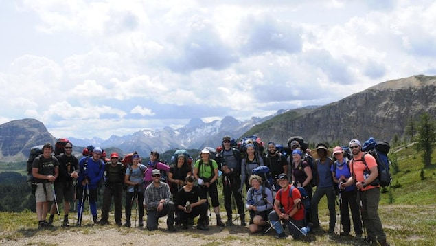 Un groupe de jeunes est réuni pour prendre une photo au sommet d'une montagne. À l'arrière, on voit les Rocheuses canadiennes.