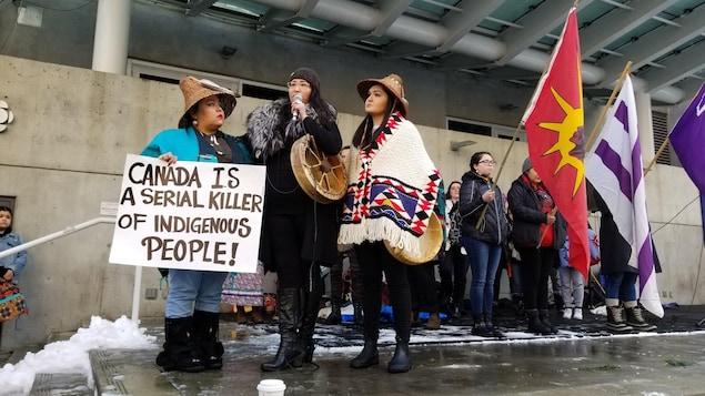 Trois femmes sur le devant de la scène, dont une est au micro et trois autres tiennent des drapeaux derrière.
