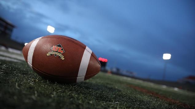 Ballon de l'équipe du Rouge et Or, de l'Université Laval, sur le sol du terrain de football du PEPS. Le ciel est couvert et le soleil sera bientôt couché. On distingue des morceaux de glace et de neige au loin sur le terrain.