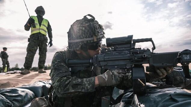 Un soldat équipé tire sous l'oeil d'un autre soldat qui supervise les opérations