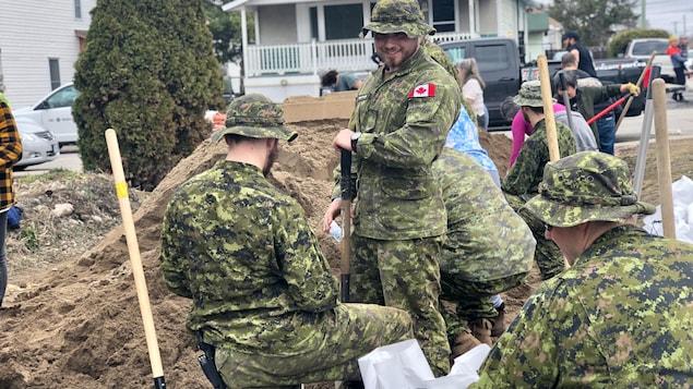 Des soldats tenant des pelles alors qu'ils remplissent des sacs de sable.