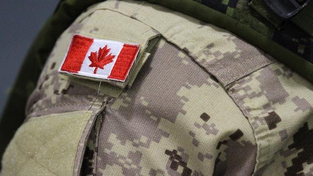 Zoom sur le drapeau du Canada qui figure sur l'uniforme porté par un militaire.