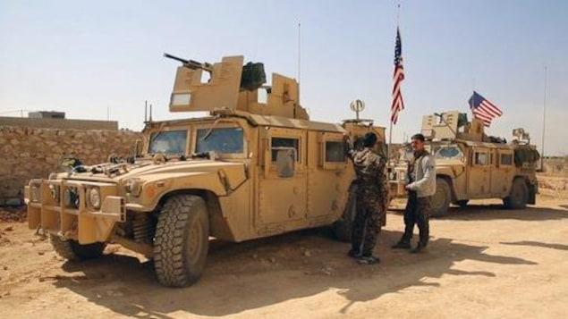 Des combattants des Forces démocratiques syriennes (FDS) près de véhicules militaires américains aux abords de Manbij, dans la province d'Alep, en Syrie, le 7 mars 2017, soit deux mois avant l'offensive menée à Raqqa.