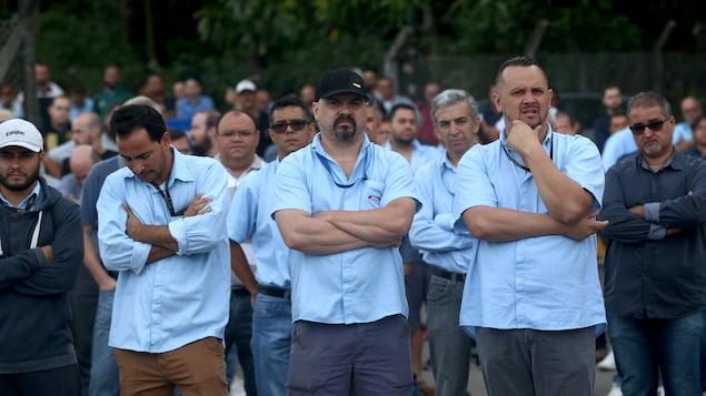 Des travailleurs manifestent après avoir appris la fermeture de leur usine.