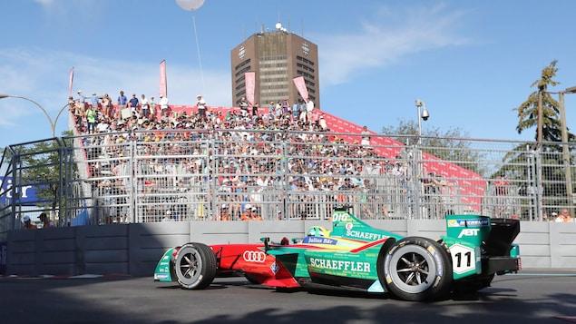 Une voiture de course électrique devant des gradins chargés.