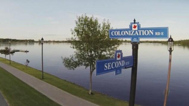 Sur le bord d'une rivière, un chemin avec une pancarte où on voit le nom des rues Colonisation et Second street.