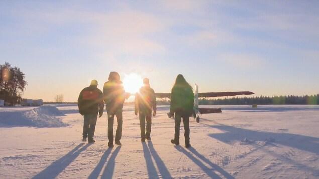 Quatre hommes marchent vers un avion.