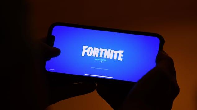 Des mains tiennent un téléphone intelligent affichant la page de chargement du jeu Fortnite.