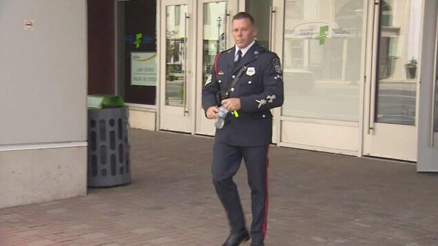Le policier sort du palais de justice.