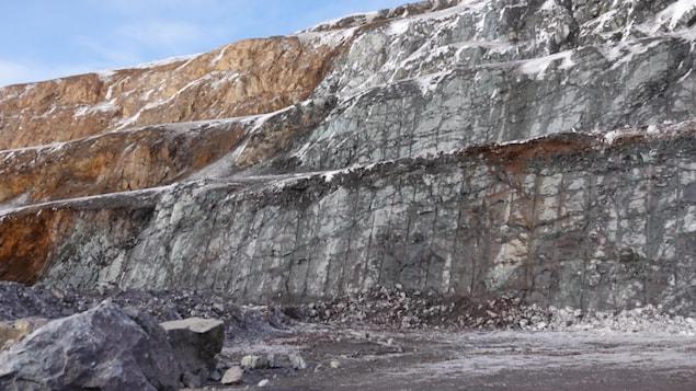La paroi rocheuse de la fosse est grise et marron.