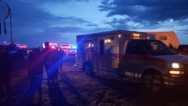 Une ambulance et des personnes sur un terrain sous un ciel nuageux.