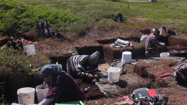 Trois personnes à genoux en train de faire des fouilles archéologiques