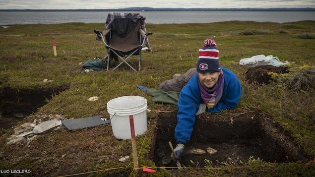 Une jeune innue en train de fouiller un carré de terre.