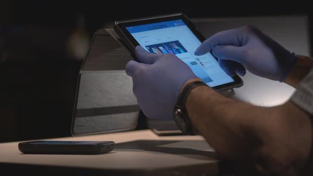 Les mains d'un douanier qui scrute un compte Facebook sur une tablette numérique.