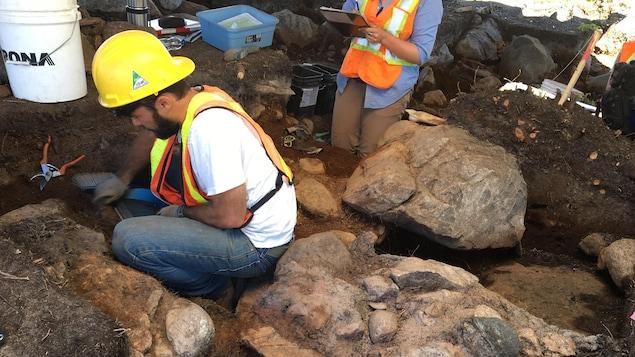 Un travailleur portant un casque agenouillé en train de fouiller