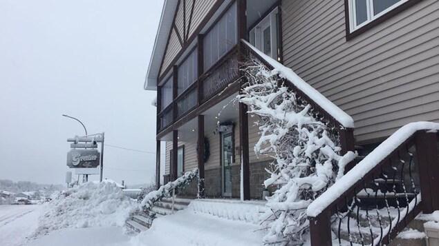Un bâtiment avec une affiche de Fourrures Grenier, en hiver.