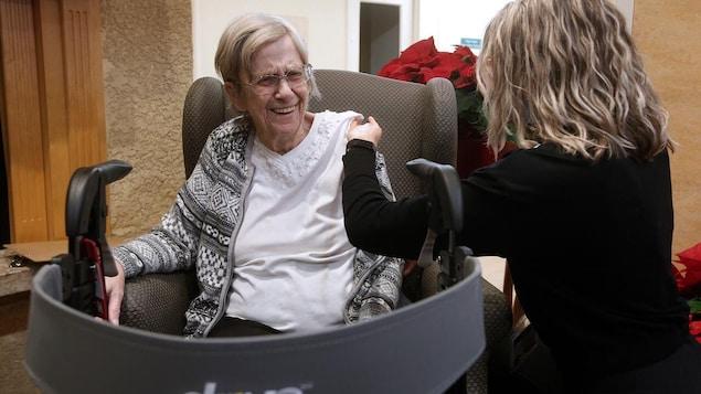 Margaret Watson sourit en recevant un vaccin dans le bras gauche.
