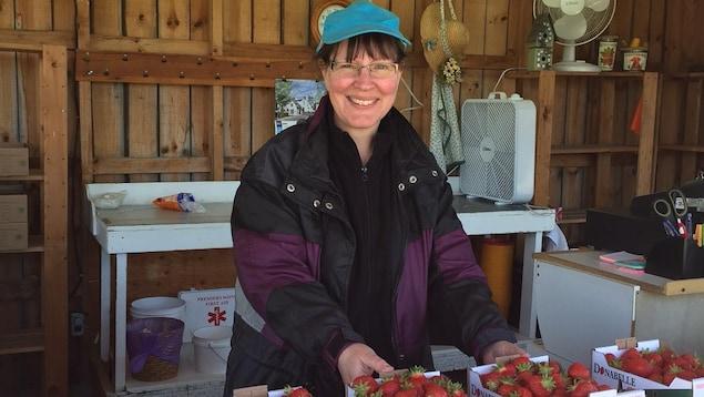 Une employée de la ferme Donabelle prend la pose devant les premières fraises de la saison.