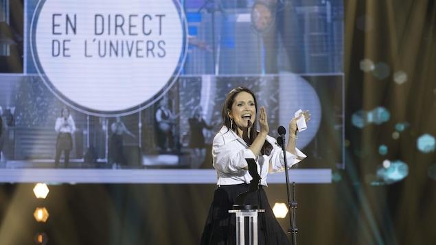 Une femme applaudit devant un micro sur scène.
