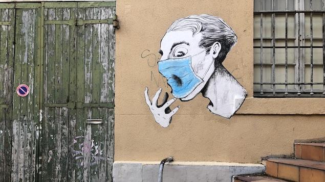 Un graffiti représente une personne portant un masque.