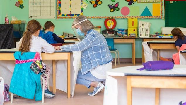 France Fournier est accroupie près du bureau d'une élève. Elle porte une visière et un masque.