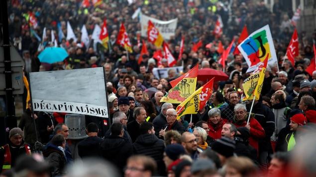 Les manifestants tiennent des drapeaux et pancartes, dont l'une porte la mention « décapitalisme ».