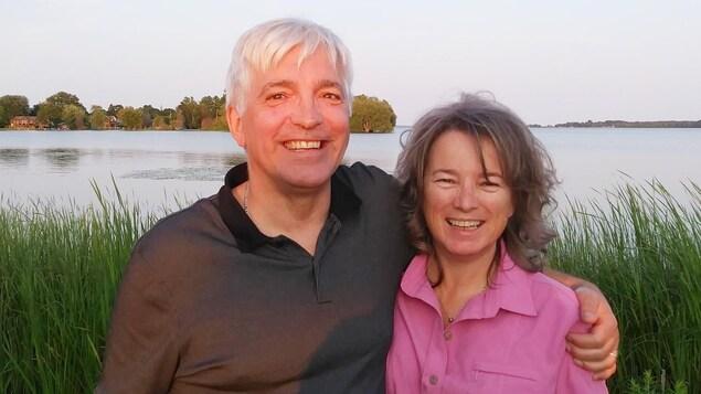 Photo des deux personnes, dans la cinquantaine, devant un lac.