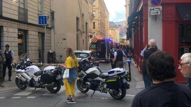 Une rue de Lyon bouclée par deux motos de policiers, avec policiers et ambulanciers sur place.