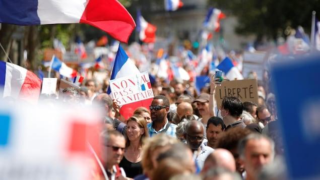 Des manifestants, des pancartes anti-pass sanitaire et des drapeaux français.