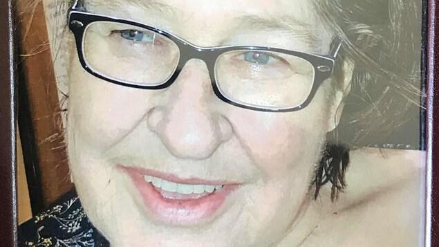 Le visage d'une femme, souriante, portant des lunettes.