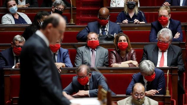 Des députés portent des masques de protection à l'Assemblée nationale à Paris.