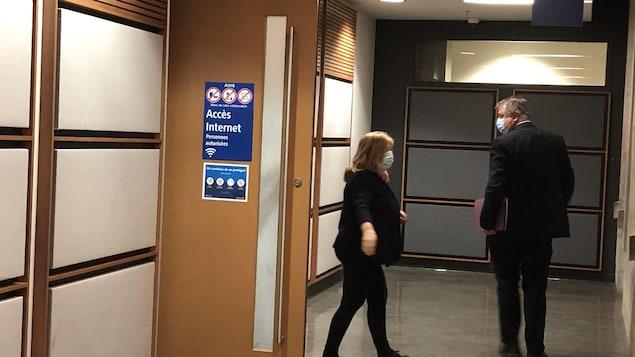Une femme et un homme dans le couloir du palais de justice.
