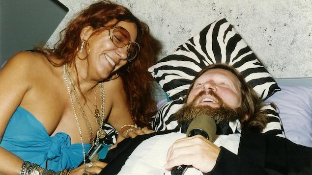 La chroniqueuse Francine Grimaldi et l'animateur Joël Le Bigot, rigolant étendus sur un lit lors d'une émission spéciale.