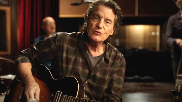Francis Cabrel chante, avec une guitare, dans une petite salle avec des musiciens derrière lui