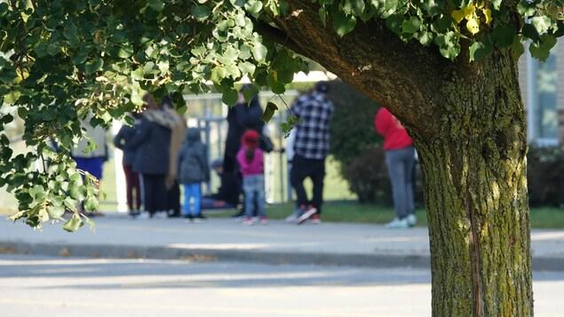 Une file d'attente de familles à l'extérieur.