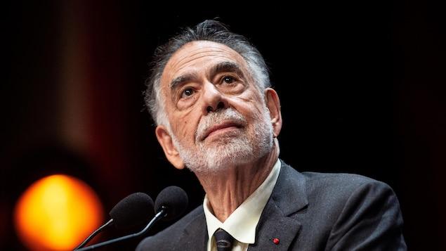 Le cinéaste Francis Ford Coppola regarde de côté vers le haut devant deux microphones.
