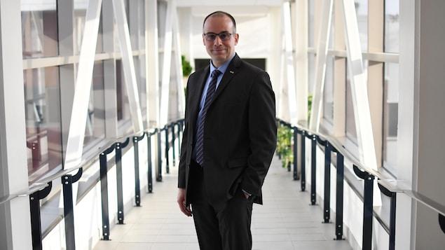 François Deschênes est debout dans un couloir vitré.