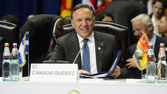 François Legault, assis à une table, lors d'une séance plénière de l'OIF.