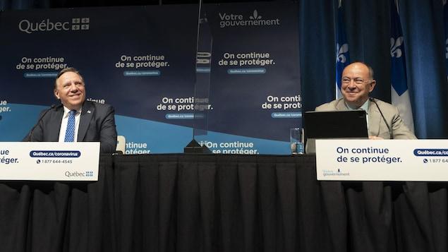 François Legault et Christian Dubé sont assis à la table de presse et sourient.