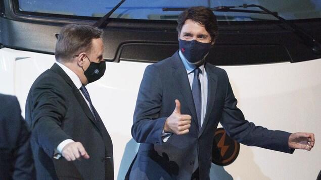 François Legault et Justin Trudeau portant un masque sont debout l'un à côté de l'autre.