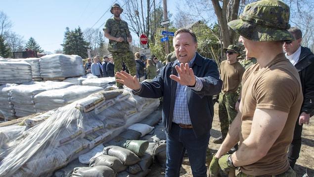 Un homme qui porte des jeans et un manteau discute avec des militaires qui remplissent des sacs de sable.