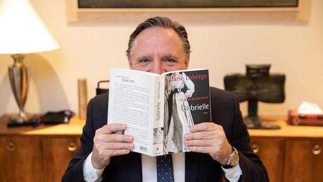 L'homme tient le premier tome de la trilogie, « Gabrielle », dans ses mains, devant son visage.