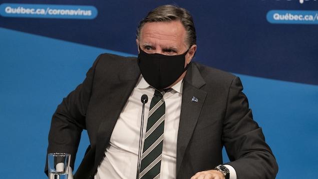 Le premier ministre du Québec François Legault, porte un masque à son arrivée à la conférence de presse.