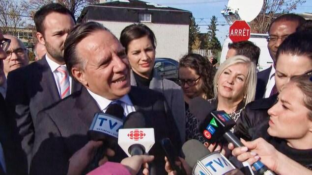 Le premier ministre parle aux médias à Gatineau, accompagné d'autres politiciens.