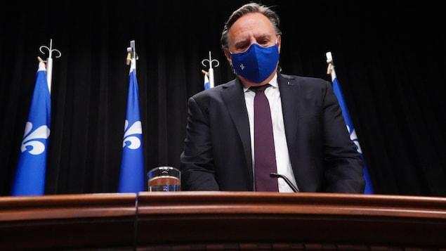 François Legault, debout derrière un bureau et devant des drapeaux du Québec, portant un masque.